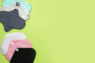 Many reusable cloth menstrual pads on green background, flat lay. Space for text