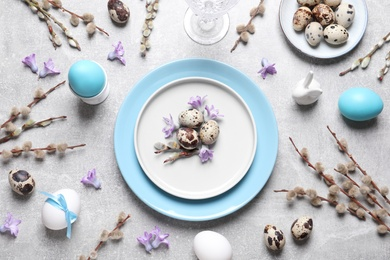 Festive Easter table setting with painted eggs and floral decor on light grey background, flat lay