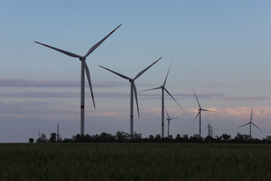 Beautiful view of landscape with wind turbines in evening. Alternative energy source
