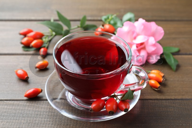 Aromatic rose hip tea and fresh berries on wooden table