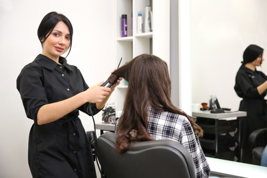 Professional female hairdresser curling client's hair in salon