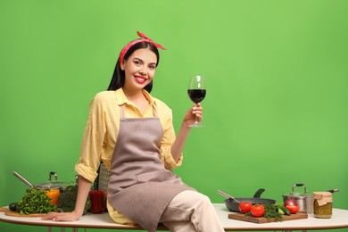 Young housewife with glass of wine, vegetables and different utensils on green background. Space for text