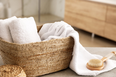 Wicker basket with clean towels and massage brush on table in bathroom