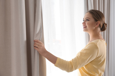 Woman opening window curtains at home in morning