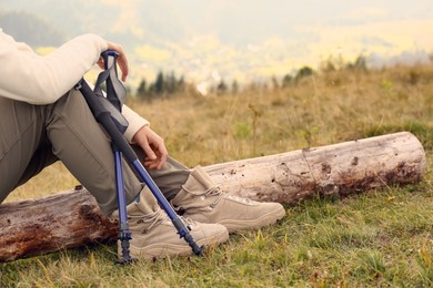 Woman with trekking poles resting during hike in mountains, closeup. Space for text