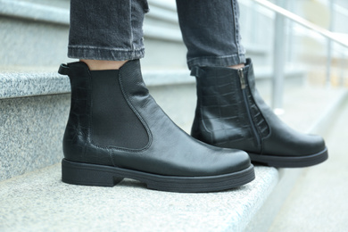 Woman in stylish boots on stairs outdoors, closeup