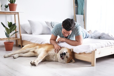 Man and Akita Inu dog in bedroom decorated with houseplants