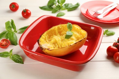 Half of cooked spaghetti squash with basil in baking dish and tomatoes on white wooden table