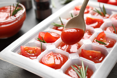 Pouring sauce into ice cube tray with tomatoes and rosemary on grey table, closeup