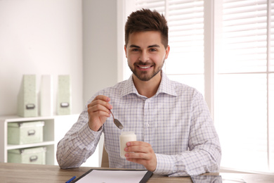 Happy young man with tasty yogurt in office