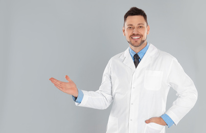 Happy man in lab coat on light grey background