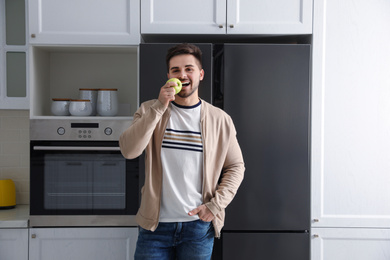 Young man eating apple near refrigerator in kitchen