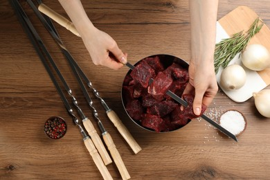 Woman stringing marinated meat on skewer at wooden table, top view