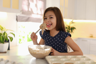 Cute little girl licking raw dough from spoon in kitchen. Cooking food