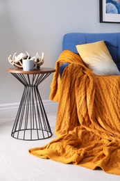 Soft knitted blanket on armchair in room. Home interior