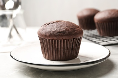 Delicious chocolate cupcake on light grey marble table, closeup