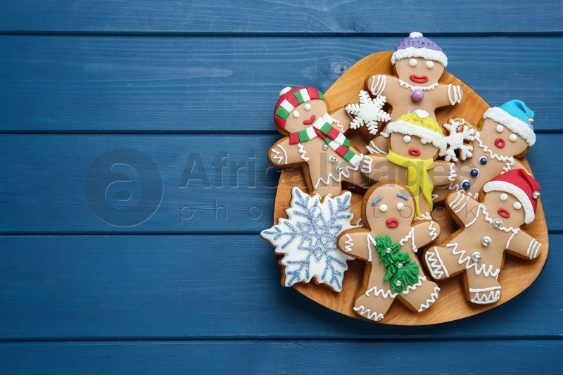 Delicious Christmas cookies on blue wooden table, top view. Space for text