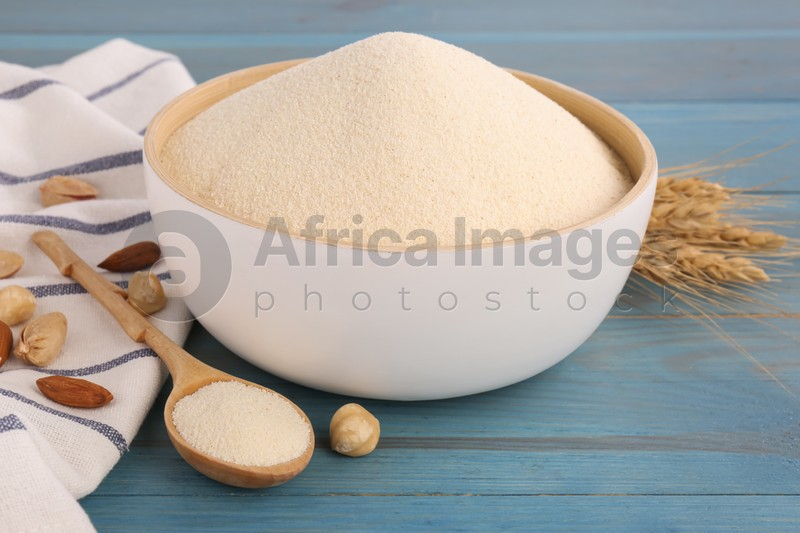 Uncooked organic semolina, spikelets and different nuts on light blue wooden table