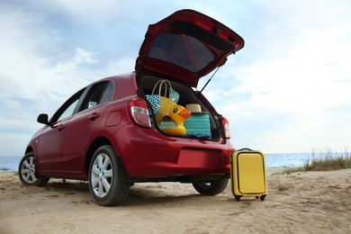Red car with luggage on beach. Summer vacation trip