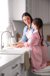Mother and daughter washing dishes together in kitchen