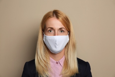Woman wearing handmade cloth mask on beige background. Personal protective equipment during COVID-19 pandemic