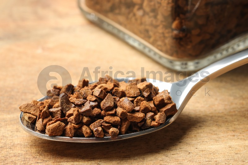 Spoon of chicory granules on wooden table, closeup