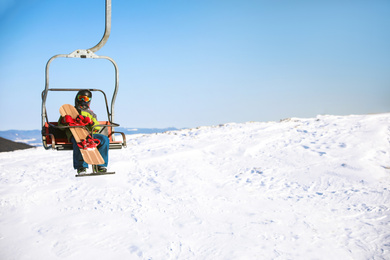 Man using chairlift at mountain ski resort, space for text. Winter vacation