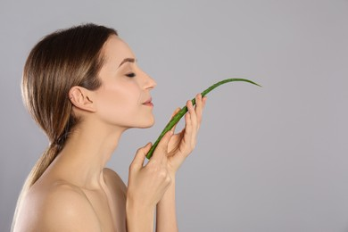 Young woman with aloe leaf on light grey background