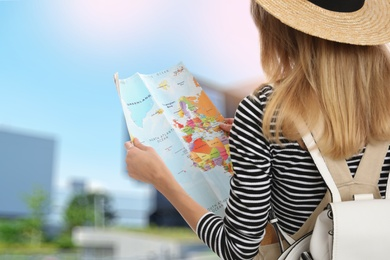 Happy traveler with map in foreign city. Summer vacation trip