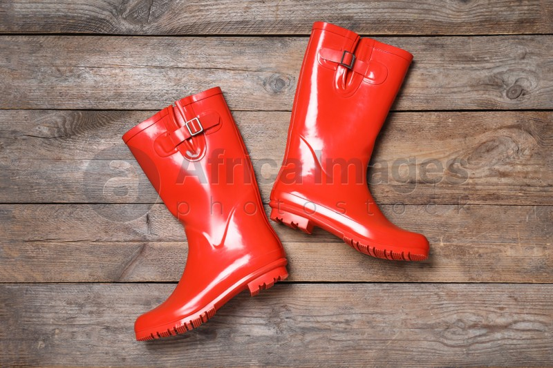 Pair of red rubber boots on wooden background, top view