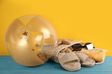 Bright inflatable ball and bag with beach accessories on light blue wooden table against yellow background