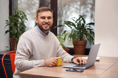 Male blogger working with laptop at table in cafe