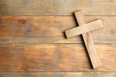 Christian cross on wooden background, top view with space for text. Religion concept