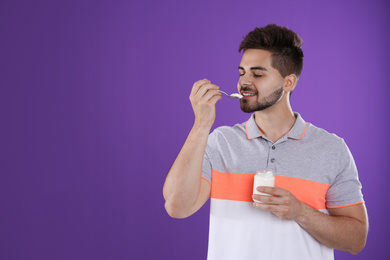 Happy young man eating tasty yogurt on purple background. Space for text