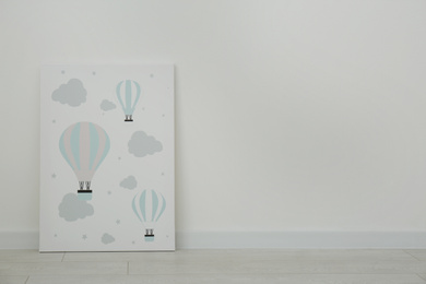 Adorable picture of air balloons on floor near white wall, space for text. Children's room interior element
