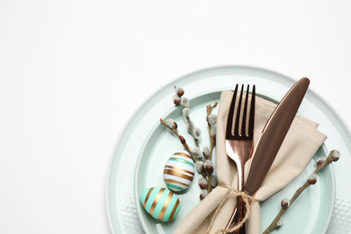 Festive Easter table setting with floral decor on white background, top view