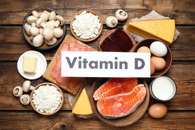 Paper with phrase VITAMIN D and fresh products on wooden table, flat lay