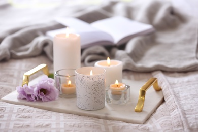 Beautiful burning candles and book on bed at home