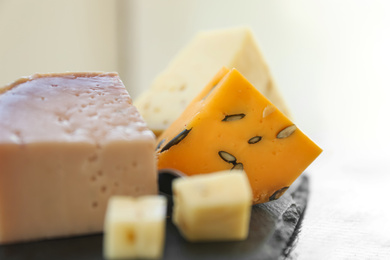 Different types of delicious cheeses on slate plate, closeup