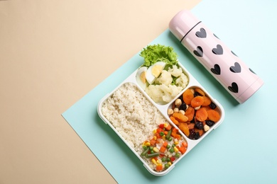 Thermos and lunch box with food on color background, flat lay. Space for text