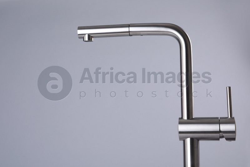 Modern pull out kitchen faucet on grey background. Space for text
