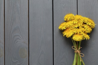 Beautiful dandelion bouquet on grey wooden table, top view. Space for text