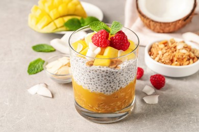 Delicious chia pudding with mango, raspberries and granola on light grey table