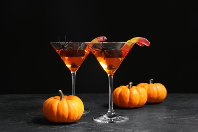 Decorated glasses with drinks on grey table. Halloween celebration