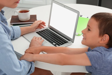 Little boy bothering mother with laptop at work in kitchen, closeup. Home office concept