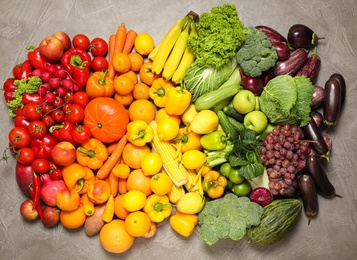 Assortment of organic fresh fruits and vegetables on grey background, flat lay