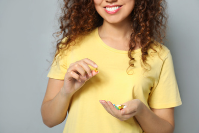 African-American woman with different vitamins on light grey background, closeup
