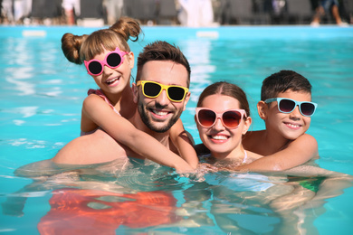 Happy family in swimming pool on sunny day