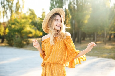 Beautiful young woman in stylish yellow dress and straw hat outdoors