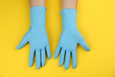 Person in medical gloves on yellow background, top view